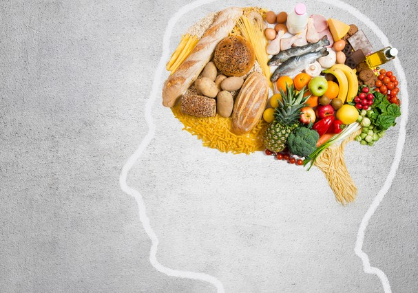 Human head shape with variety of different food ingredients on gray background (Foto: Getty Images/iStockphoto)