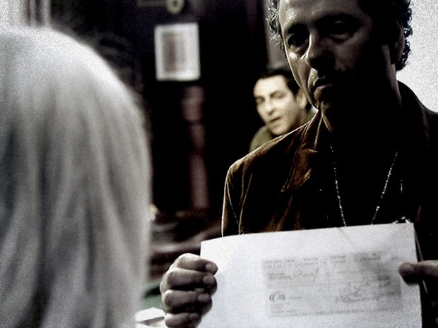 Pedroso mostra para Vic o cheque encontrado nas mãos do traficante (Foto: O Rebu / TV Globo)
