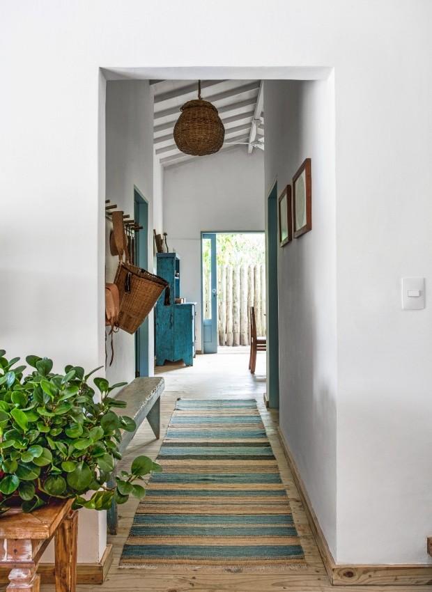 Corredor A passadeira da By Kamy traz o tom de azul que se repete nos batentes da ala íntima da casa. Pendente de palha da artesã Nádia Calazans (Foto: Marco Antonio / Editora Globo)
