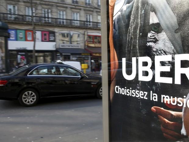 Imagem de arquivo mostra táxi passando por anúncio do Uber em ponto de ônibus em Paris (Foto: Charles Platiau/Reuters)