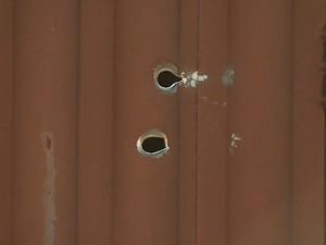 Há marcas de balas no portão da casa do agente e em imóveis vizinhos (Foto: Marlon Tavoni/EPTV)