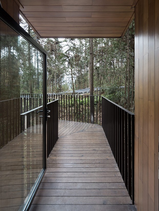 Um corredor de madeira leva os hóspedes até o quarto (Foto: Bowen hou/Divulgação)