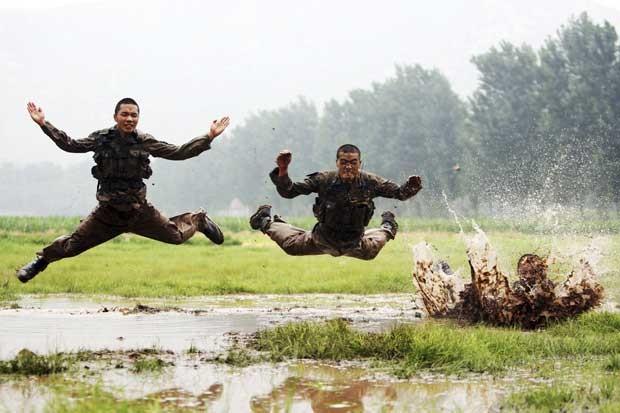 Em treinamento, soldados chineses saltam na lama. (Foto: China Daily/Reuters)