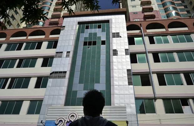 Homem olha para a fachada do edifício mais alto de Mandalay, de 25 andares, de onde várias vidraças caíram depois do terremoto de 6,8 graus de magnitude que atingiu o norte de Mianmar neste domingo (11) (Foto: AFP)