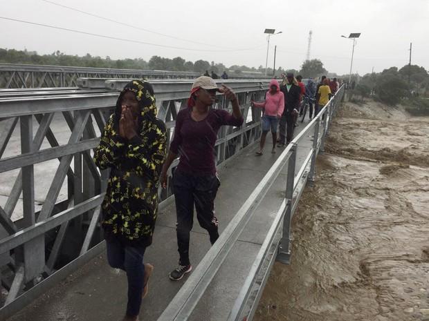 Pessoas caminham em ponte durante passagem do furacão Matthew por Porto Príncipe, no Haiti (Foto: REUTERS/Carlos Garcia Rawlins)