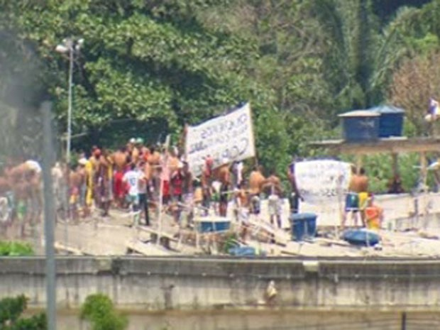 Pela manhã, presos subiram em teto de pavilhão com cartazes em protesto pacífico (Foto: Reprodução/ TV Globo)