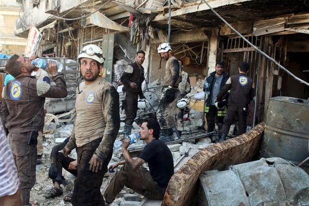 Socorristas descansam na sexta-feira (16) em meio aos escombros de edifícios danificados após um ataque aéreo no bairro de Tariq al-Bab, que é controlado pelos rebeldes em Aleppo, na Síria (Foto: Abdalrhman Ismail/Reuters)