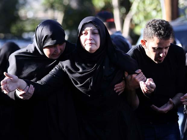 Viúva de vítima de ataque a bomba em Beirute é amparada por familiares durante seu funeral nesta sexta-feira (13) (Foto: AFP PHOTO / MAHMOUD ZAYYAT)