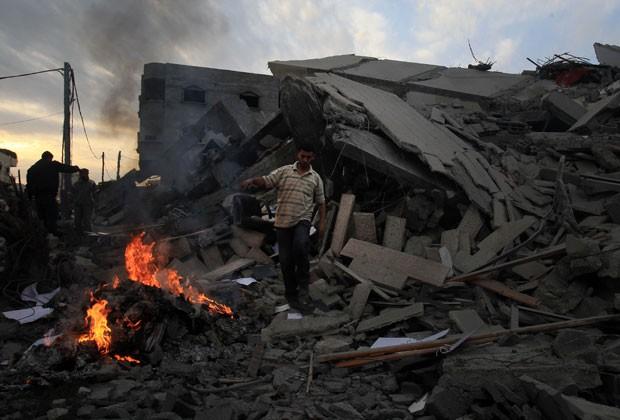 Membro das Forças de Segurança palestinas inspeciona escritório do primeiro-ministro do Hamas que foi destruído por ataque de Israel em Gaza (Foto: AFP)
