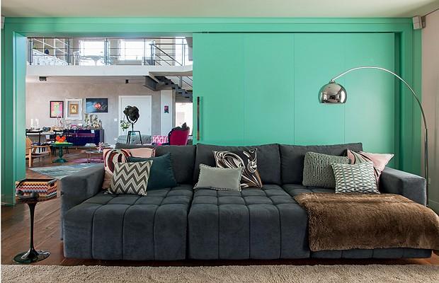 Home theater: O sofá, da Veneza, possui almofadas feitas de lenços Pucci. Formica turquesa reveste aporta divisória, ao fundo, que separa o living (Foto: Cacá Bratke)