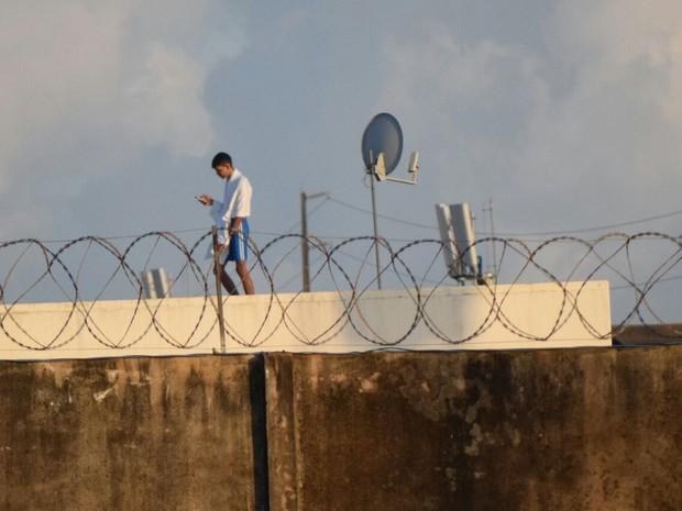 Detento usa aparelho celular do alto do pavilhão 5 de Alcaçuz  (Foto: Fred Carvalho/G1)