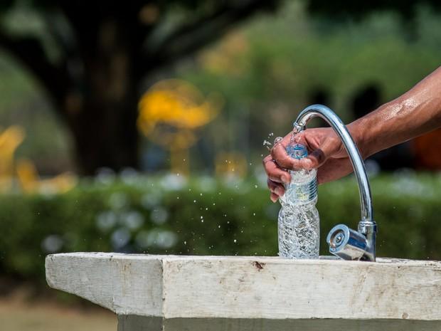 Homem enche garrafa d'água em parque na zona oeste de São Paulo (Foto: Marcelo Brandt/G1)