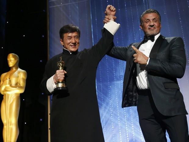 Stallone ergue o braço de Jackie Chan após a entrega do Oscar honorário ao chinês (Foto: Mario Anzuoni/Reuters)