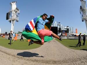 Fã de rock salta em frente ao palco Mundo, com bandeiras do Brasil e do Reino Unido nas costas (Foto: Alexandre Durão/G1)