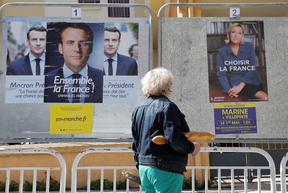 Mulher passa diante de cartazes de candidatos presidenciais franceses, Emmanuel Macron e Marine Le Pen, às vésperas do segundo turno (Foto: REUTERS/Eric Gaillard)