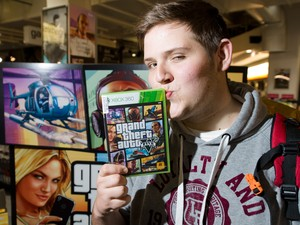 Fã do Reino Unido beija cópia de 'Grand Theft Auto V' após lançamento do game em Londres (Foto: Leon Neal/AFP)