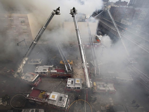 Diversos carros de bombeiros são usados para conter o fogo no local do desabamento no Harlem (Foto: John Minchillo/AP)