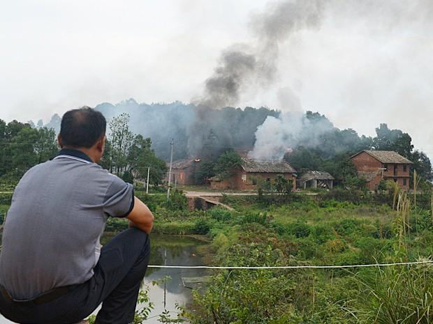 Homem olha para a fumaça de uma fábrica de fogos de artifício após uma explosão em Liling, na China (Foto: Reuters)