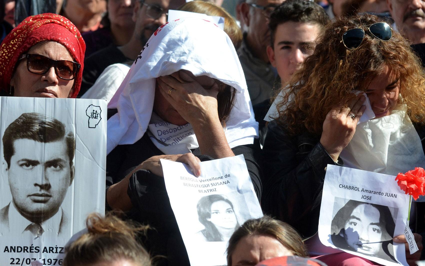 Manifestantes exibem fotos de desaparecidos no lado de fora da Corte Federal de Córdoba, na Argentina, na quinta (25), durante julgamento de militares envolvidos em crimes na ditadura (Foto: Laura Lescano/TELAM AFP/AFP)