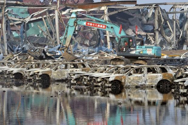 Homens trabalham em área queimada após explosão em Tianjin, na China (Foto: Chinatopix Via AP)