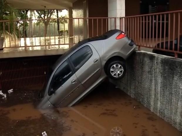 Carro amanheceu atolado em frente a garagem da 402 Norte, em Brasília, na manhã desta quarta-feira, após forte chuva (Foto: TV Globo/Reprodução)