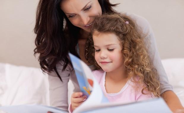 Mãe e filha lendo livro na cama (Foto: Shutterstock)