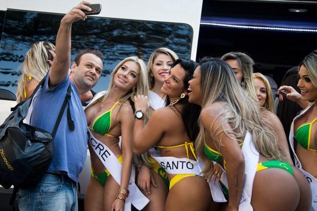 Fã faz selfie com as candidatas do Miss Bumbum (Foto: Nelson Almeida/AFP)