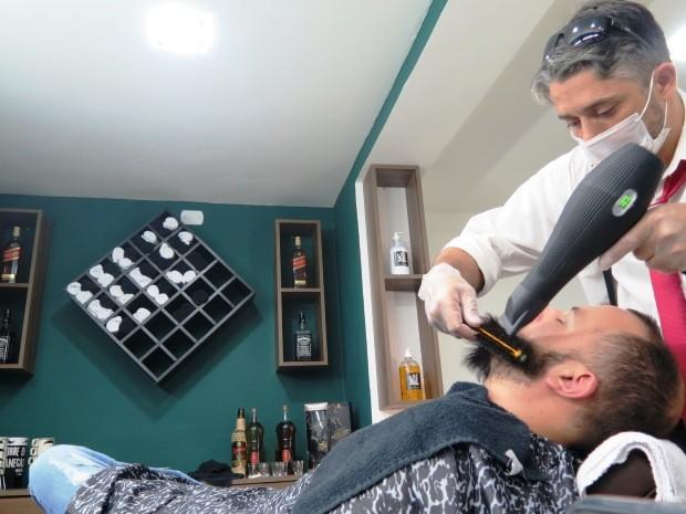 Barbeiro faz 'chapinha' em barba de cliente  (Foto: Orion Pires / G1)