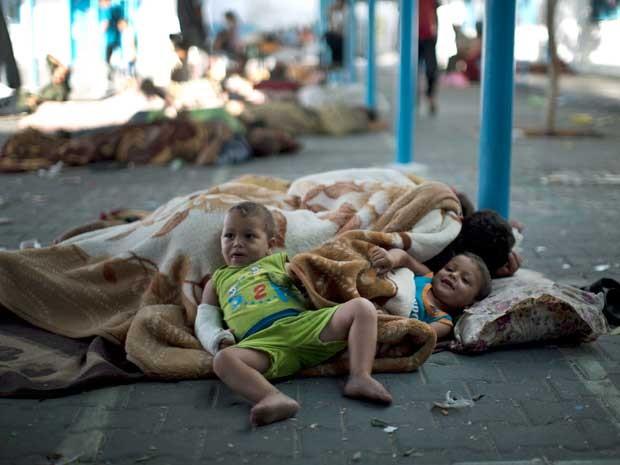 Crianças palestinas descansam em uma escola da ONU depois de deixar suas casas perto da fronteira, no campo de refugiados de Jabaliya, na Faixa de Gaza. (Foto: Mahmud Hams / AFP Photo)