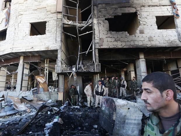 Força pró-governo da Síria inspecionam o local onde houve uma série de explosões perto de Sayyida Zeinab (Foto: Louai Beshara/ AFP)