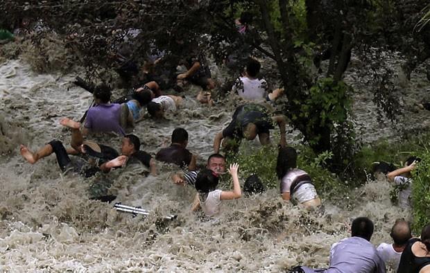 Pessoas foram arrastadas pela onda gigante vinda do rio Qiantang em Haining (Foto: Reuters/China Daily)