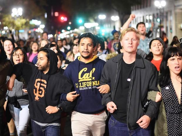 Manifestantes caminham de braços dados em marcha contra o presidente eleito dos EUA, Donald Trump, em uma rua de Oakland, na Califórnia. Um grupo diferente ateou fogo a barricadas e quebrou janelas pela cidade também em protesto (Foto: Noah Berger/Reuters)