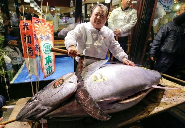Kiyoshi Kimura, do grupo de restaurantes Sushi Zanmai, posa em frente a atum de 405 kg (Foto:  EFE/KIMIMASA MAYAMA)