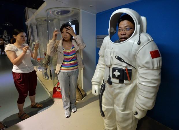 Homem 'experimenta' veste de taikonauta em uma exposição no Museu de Ciência e Tecnologia, em Pequim. (Foto: AFP Photo / Mark Ralston)