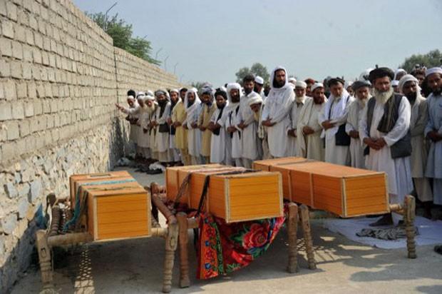 Afegãos rezam neste sábado em frente a caixões de vítimas do ataque da Otan (Foto: Noorullah Shirzada/AFP)