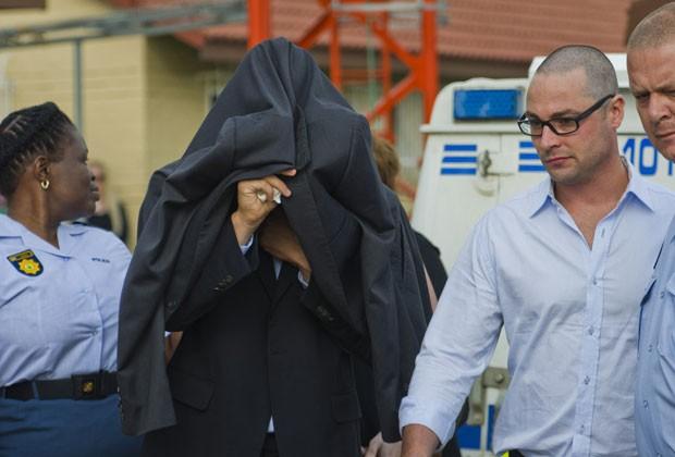 Oscar Pistorius, com o rosto coberto, é levado de delegacia para a corte de Pretória nesta sexta-feira (15). Ele participa de audiência pela morte de sua namorada (Foto: AP)