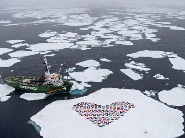 Um coração formado por 193 bandeiras de países-membros da Organização das Nações Unidas foi montado no Ártico pelo Greenpeace. A intenção da ONG é alertar para o risco de desaparecimento da região pela mudança climática e ações humanas, como exploração de (Foto: Danile Beltra/Greenpeace/AFP)