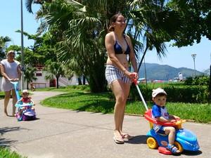 Família passeia com crianças no jardim da praia de Santos, SP (Foto: Orion Pires / G1)