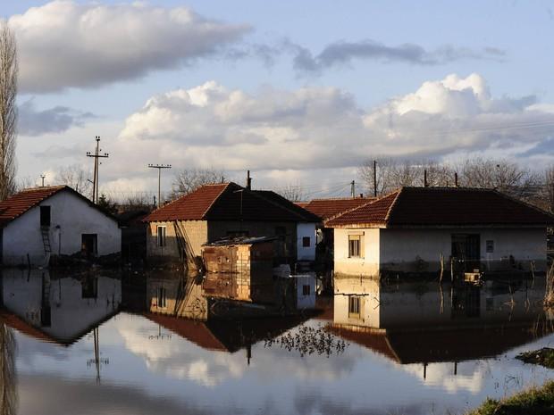 Casas e seus reflexos são vistos em um quintal inundado na Macedônia. Um homem morreu afogado e centenas de casas foram alagadas nesta terça-feira (26) na região (Foto: REUTERS / Ognen Teofilovski)