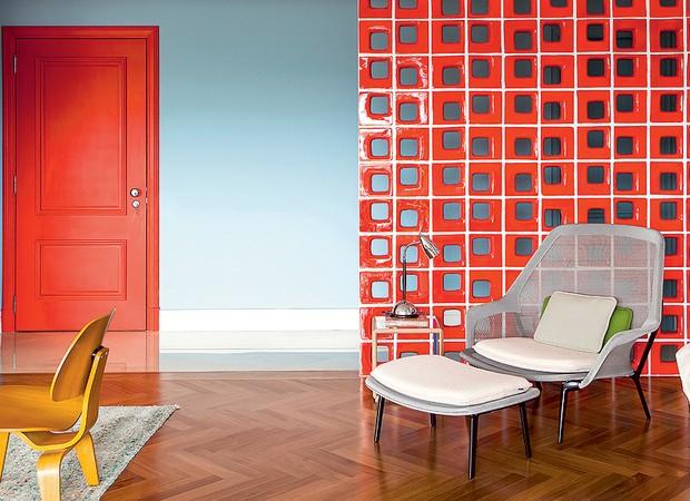 O contraste do azul com o vermelho é o que dá personalidade ao espaço. Além de disfarçar a porta do lavabo, os cobogós viabilizam a presença da poltrona – sem eles, o móvel ficaria fora de contexto na sala. Projeto da arquiteta Patrícia Martinez (Foto: Edu Castello/Casa e Jardim)