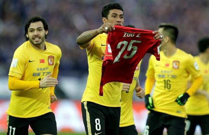 Paulinho comemora seu gol mostrando camisa do zagueiro Zou Zheng, que sofreu fratura no Mundial (Foto: EFE)