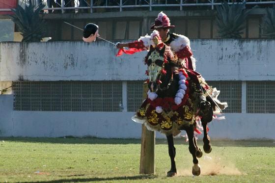 Um cavalheiro mouro enfia sua espada em uma das cabeças de papel no campo das Cavalhadas (Foto: © Haroldo Castro/Época)