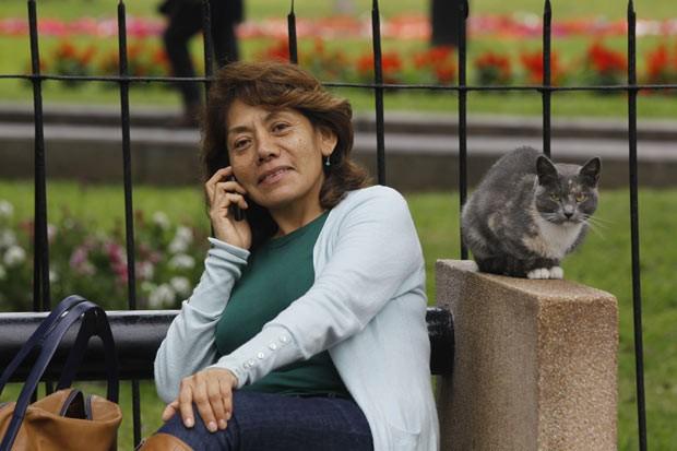 Mulher fala ao celular ao lado de gato nesta quinta-feira (2) em parque de Lima, no Peru (Foto: Martin Mejia/AP)