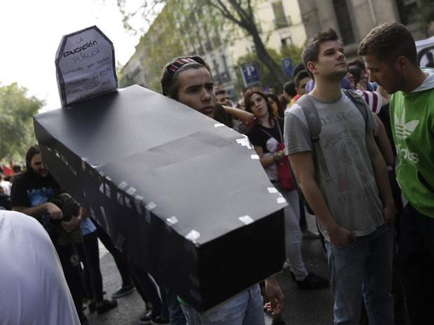 Jovem carrega caixão para simbolizar a morte da educação pública na Espanha (Foto: Andreas Comas/Reuters)