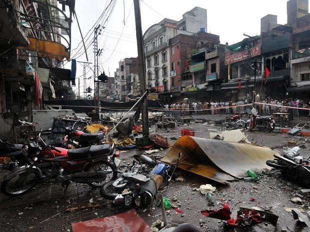 Moradores se reúnem no local de uma explosão de uma bomba em um parque de alimentos em Lahore (Foto: Arif Ali/ AFP)