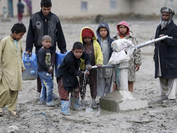 Crianças bebem água de uma bomba da rede pública nos arredores de Cabul, no Afeganistão (Foto: Omar Sobhani/Reuters)