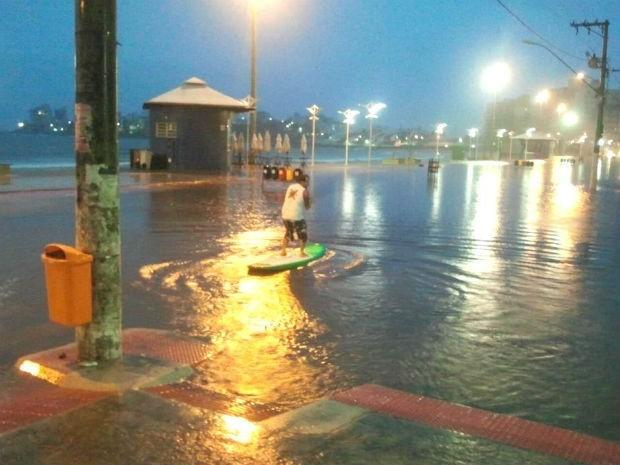 Chuva forte alagou a orla da Praia do Morro e morador saiu de casa com prancha (Foto: Vinícius Nascimento / VC NO ESTV)