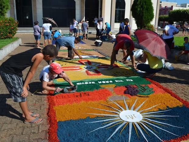 Tradição de enfeitar ruas com tapetes ultrapassa gerações (Foto: Rogério Aderbal/G1)