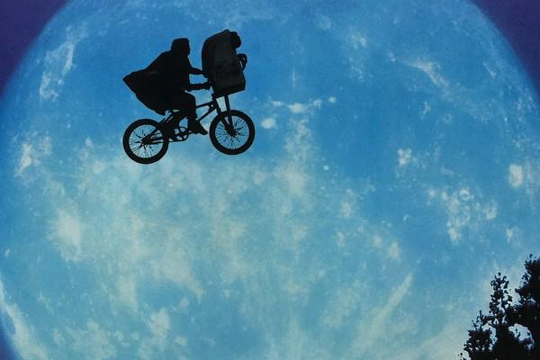 Imagem símbolo do filme, com Elliott e E.T. dando uma 'voltinha' de bicicleta sob a luz do luar (Foto: Divukgação)
