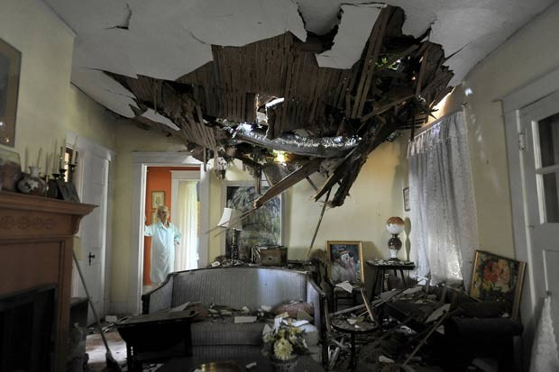 Frances Lukens observa estragos provocado por queda de árvore em sua casa em Lynchburg, na Virgínia. (Foto: Parker Michels-Boyce/The News & Advance/AP)